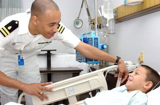 800px-US_Navy_040915-N-0000W-121_Lt._Charles_Dickerson_checks_on_a_young_patient_in_Ward_5B_of_the_U.S._Naval_Hospital,_Yokosuka